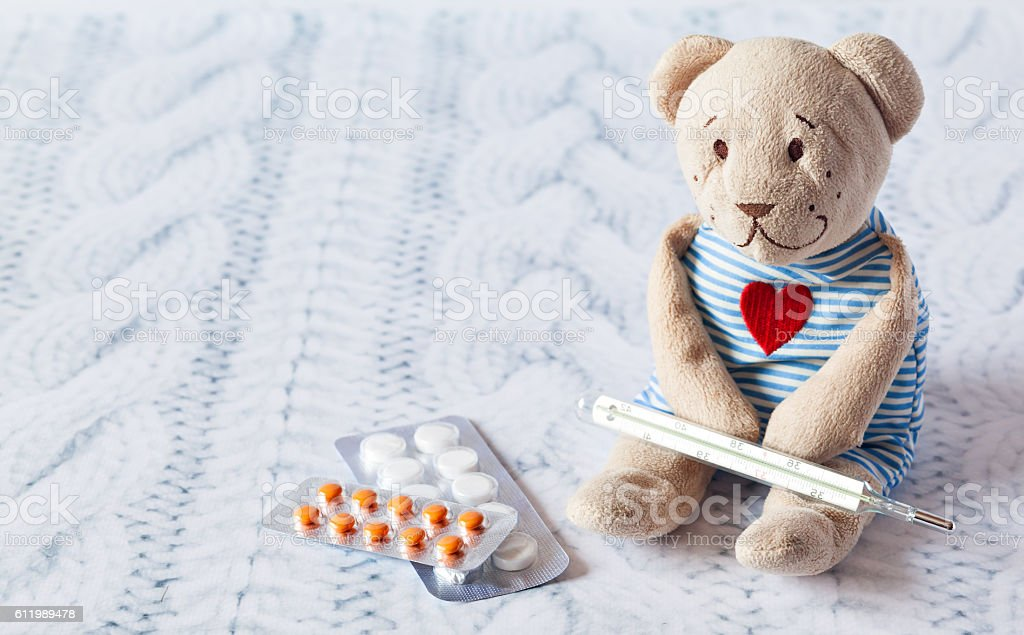 children's soft toy teddy bear with pills takes the stock photo