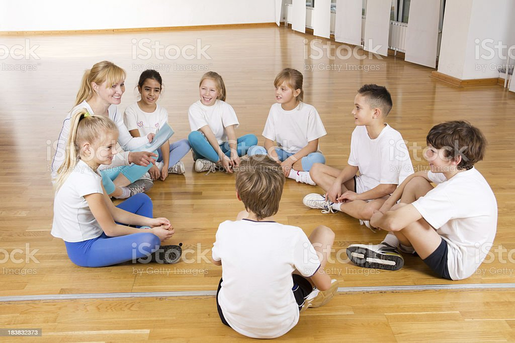 Children's sports team and female coach talking at gym. royalty-free stock photo