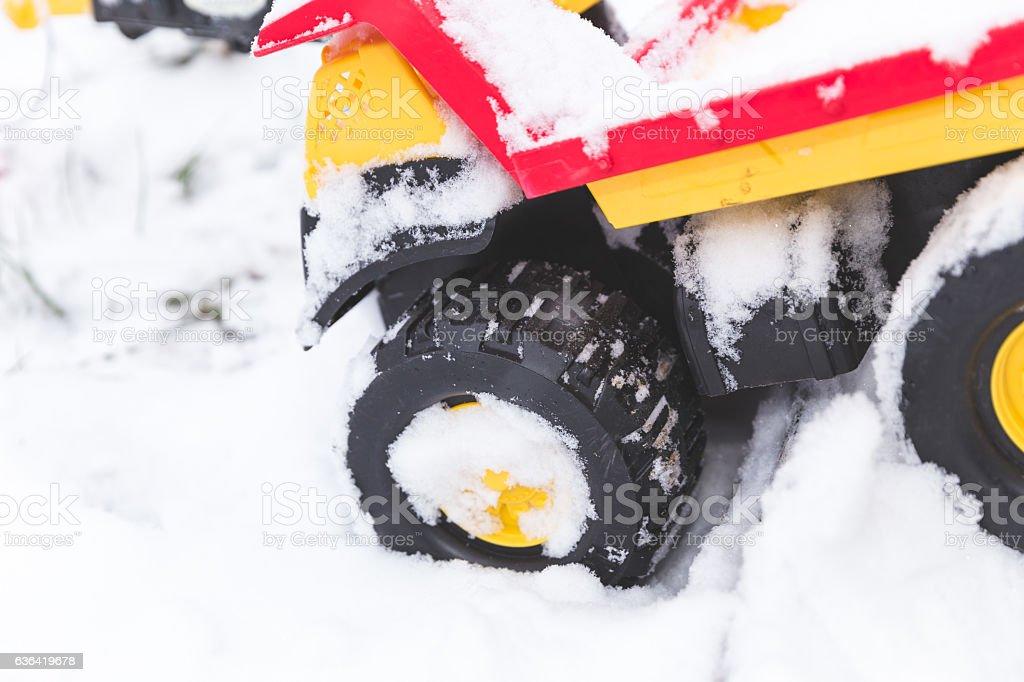 Children's toy dump truck in winter snow stock photo