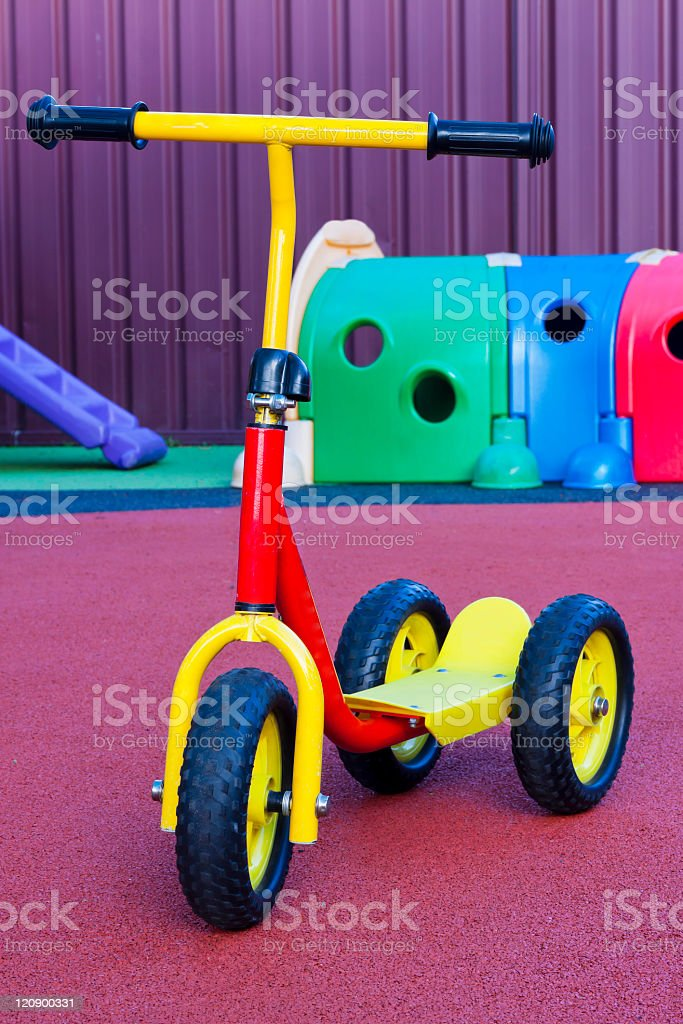Child's colourful scooter with three wheels in playground stock photo