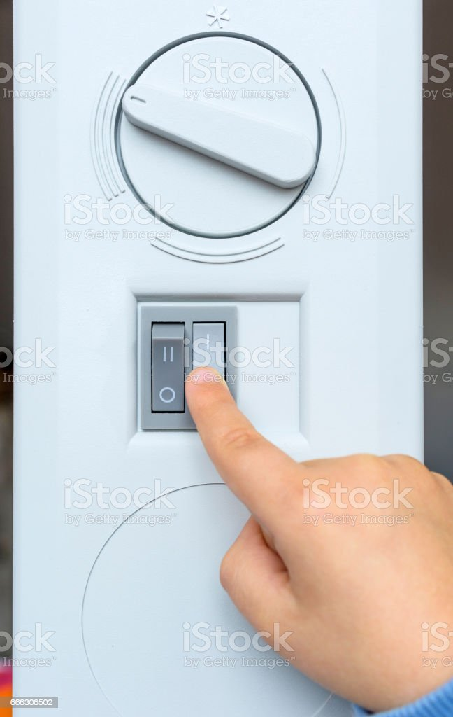 Child's Hand Adjusting Electric Heater Thermostat in winter time. stock photo