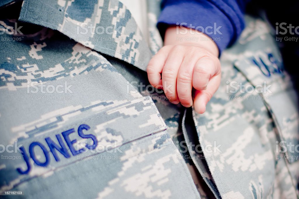 A child's hand and arm draped across an Air Force uniform stock photo