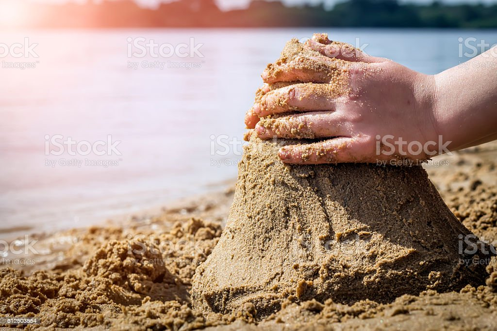 Child's hand build stronghold in salt white sand and. stock photo