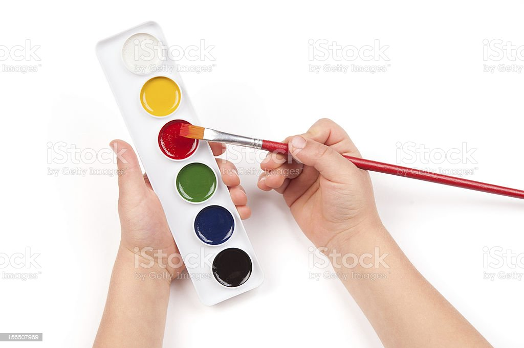 child's hand dips the brush in watercolor royalty-free stock photo