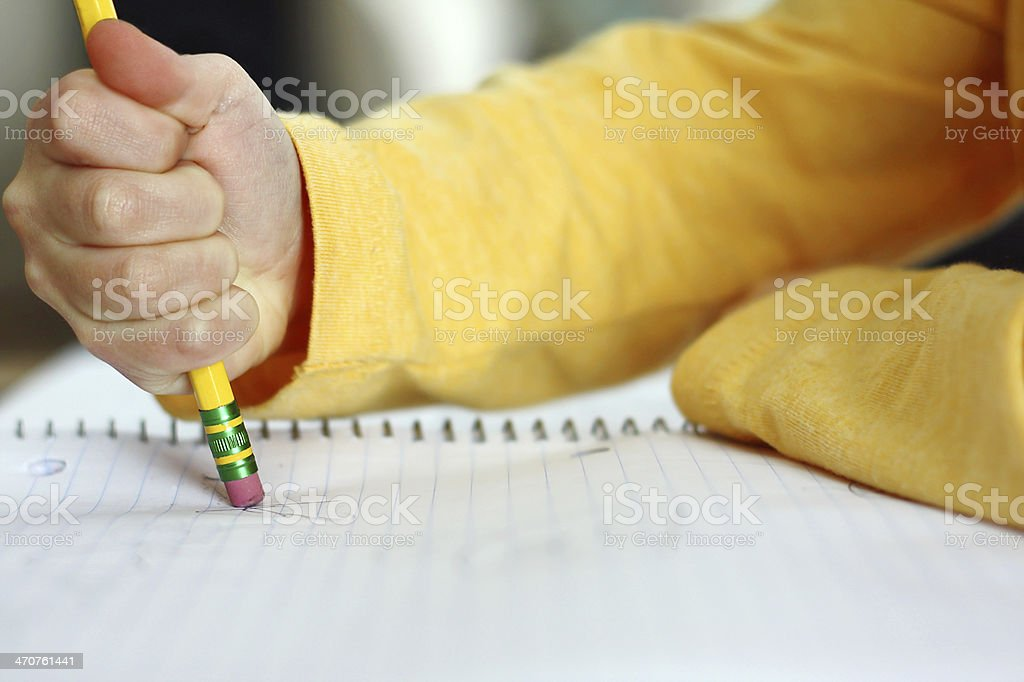 Child's Hand Erasing with Pencil on Notebook Paper stock photo