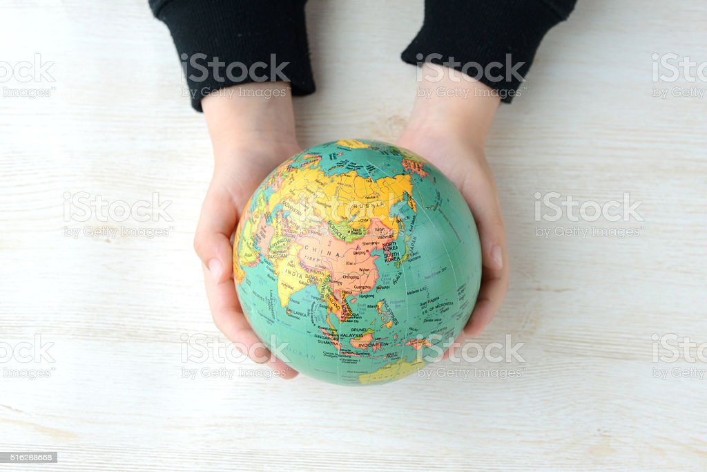 Child's hand having terrestrial globe stock photo