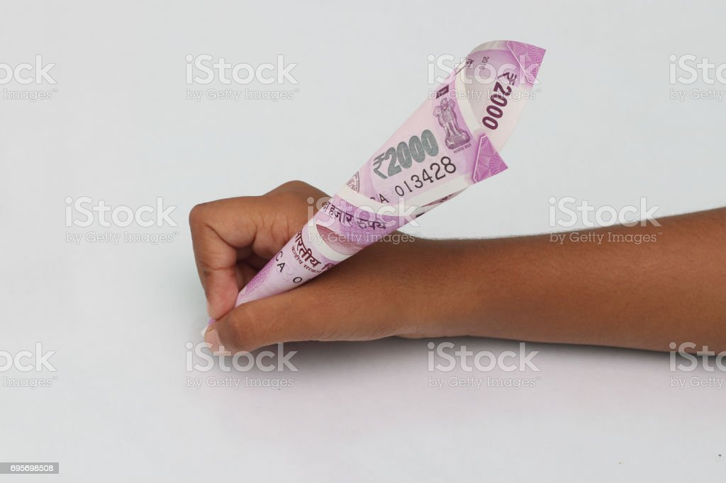 Child's hand hold 2000 rupee note just like a pen. stock photo