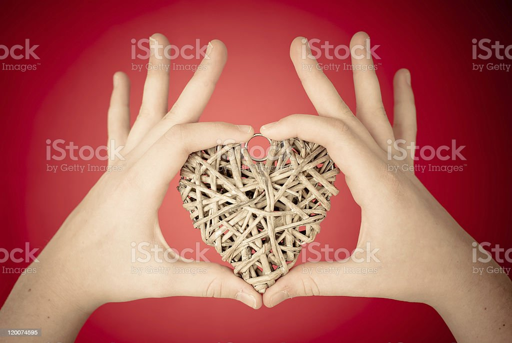 Child's Hand Holding a Heart-Shaped wood on Red Background stock photo
