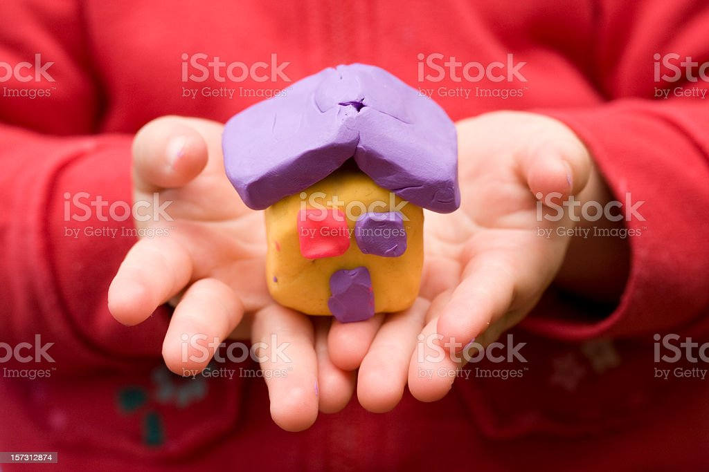 Child's hand holding small play-doh house stock photo