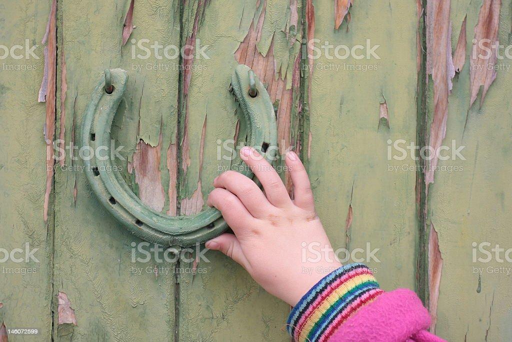 Child's hand on door knocker stock photo