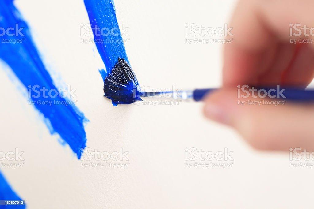 Child's hand painting blue streaks stock photo