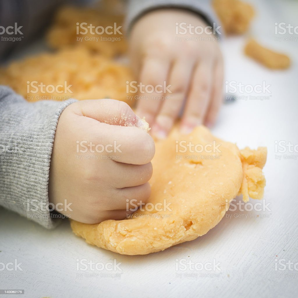 Child's hand pounding colourful dough stock photo