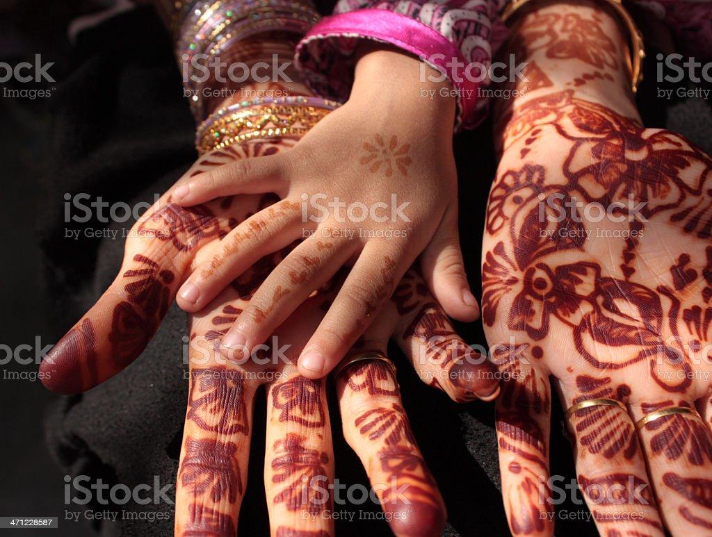 Child's hand touching adult's henna tattooed hands stock photo