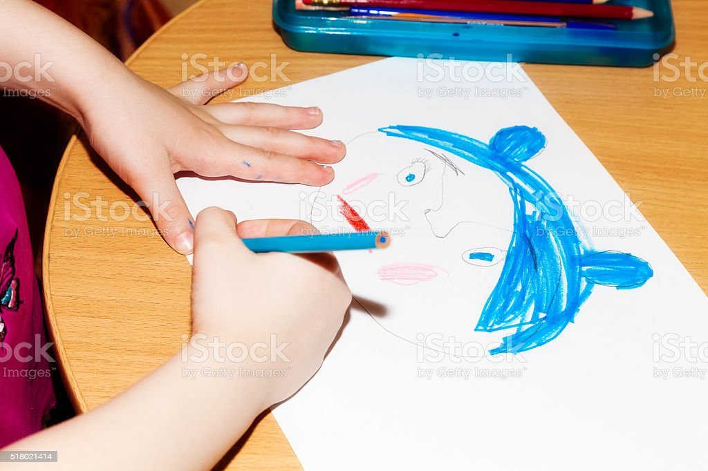 Child's hands drawing a picture on paper stock photo