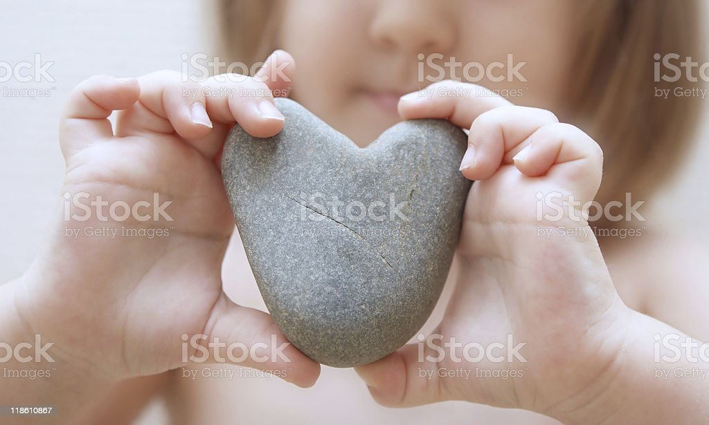 Child's hands hold heart stock photo