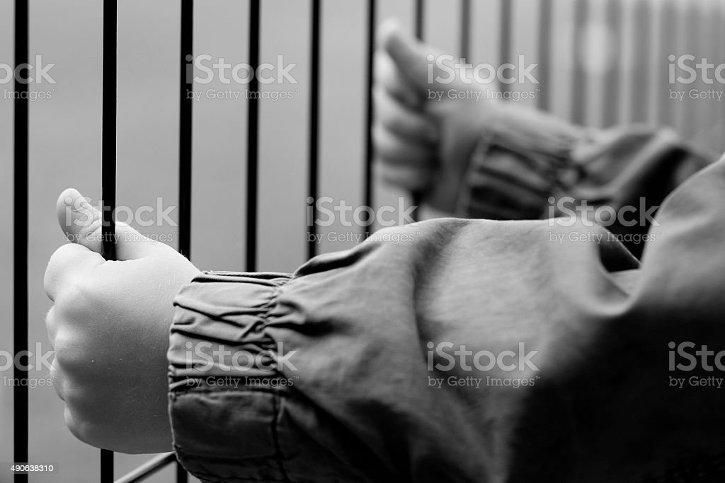 Child's hands holding a metal fence stock photo