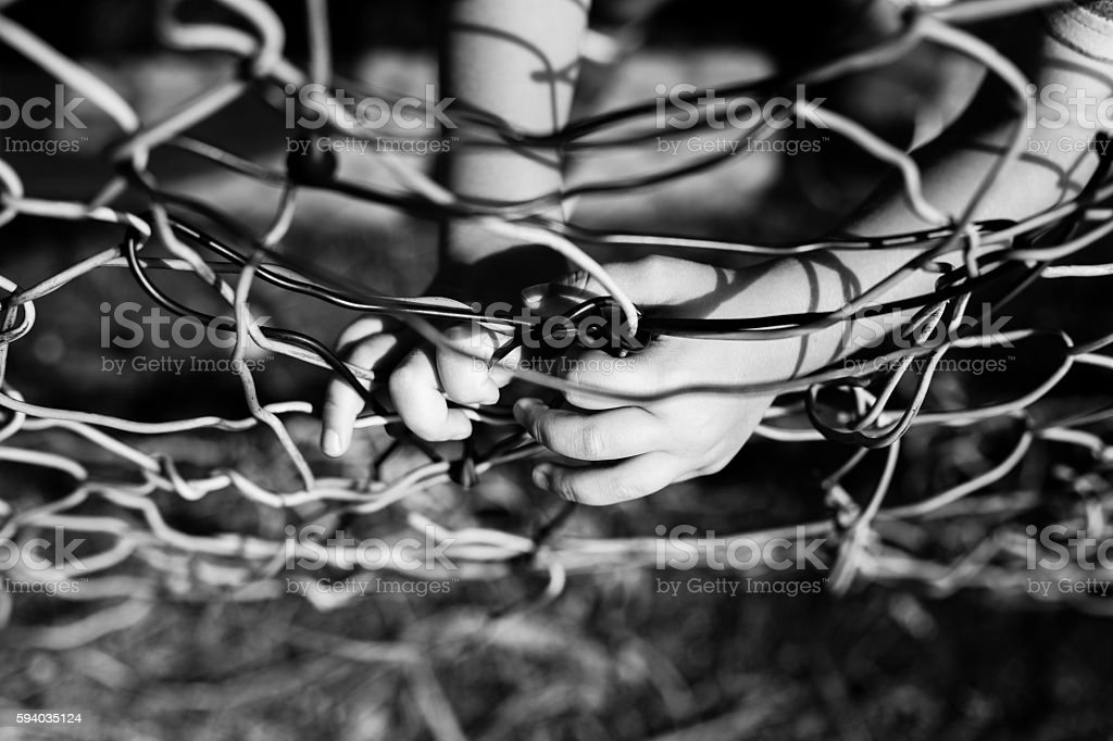 Child's hands holding fence stock photo