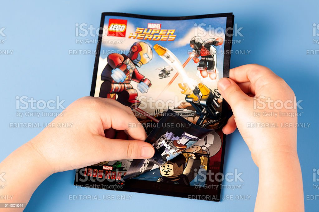 Childs hands open comic book Lego Marvel Super Heroes stock photo