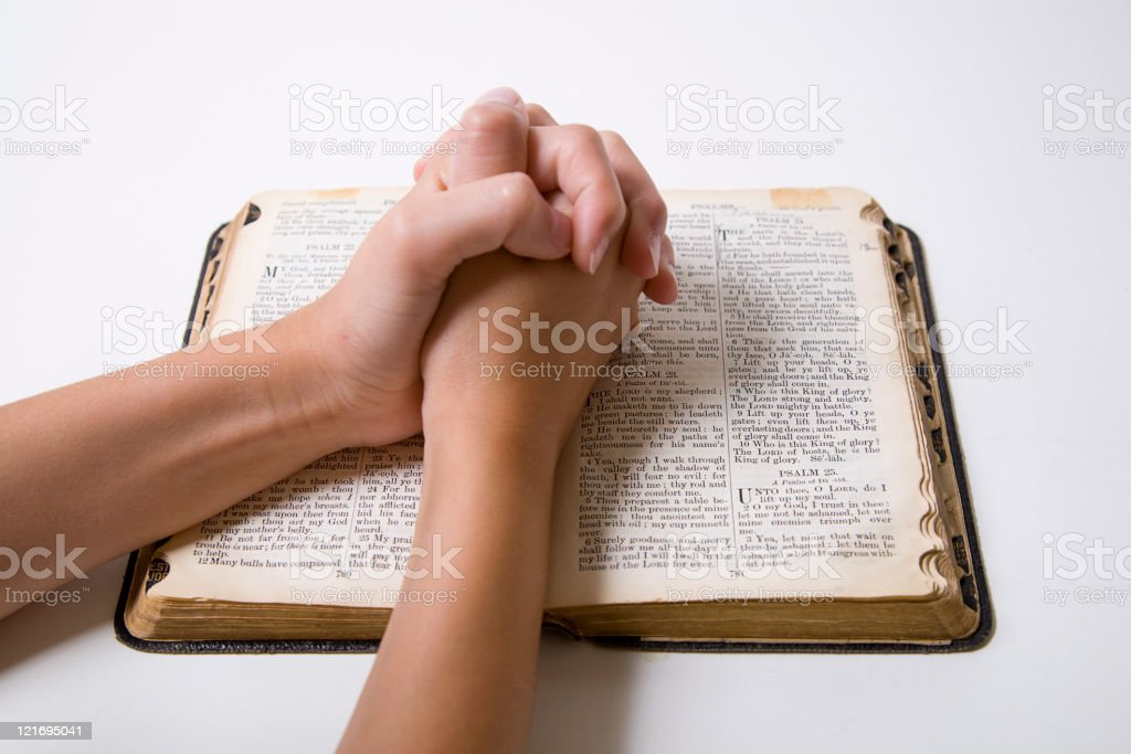 Child's Hands Praying over Bible stock photo