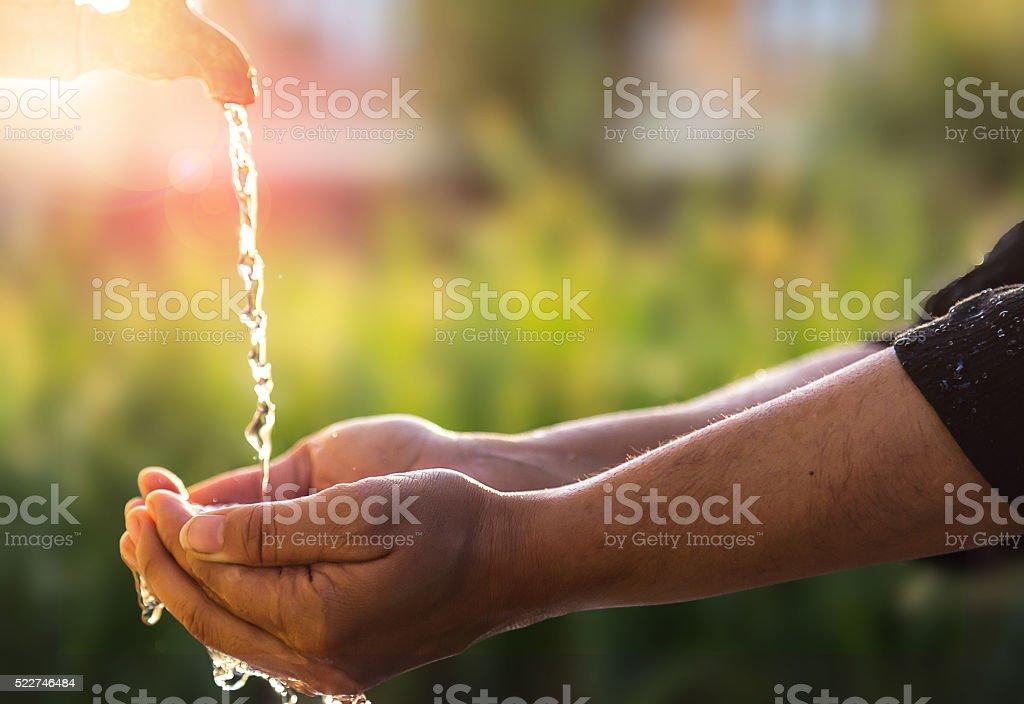 Child's Hands Under Water Tap stock photo