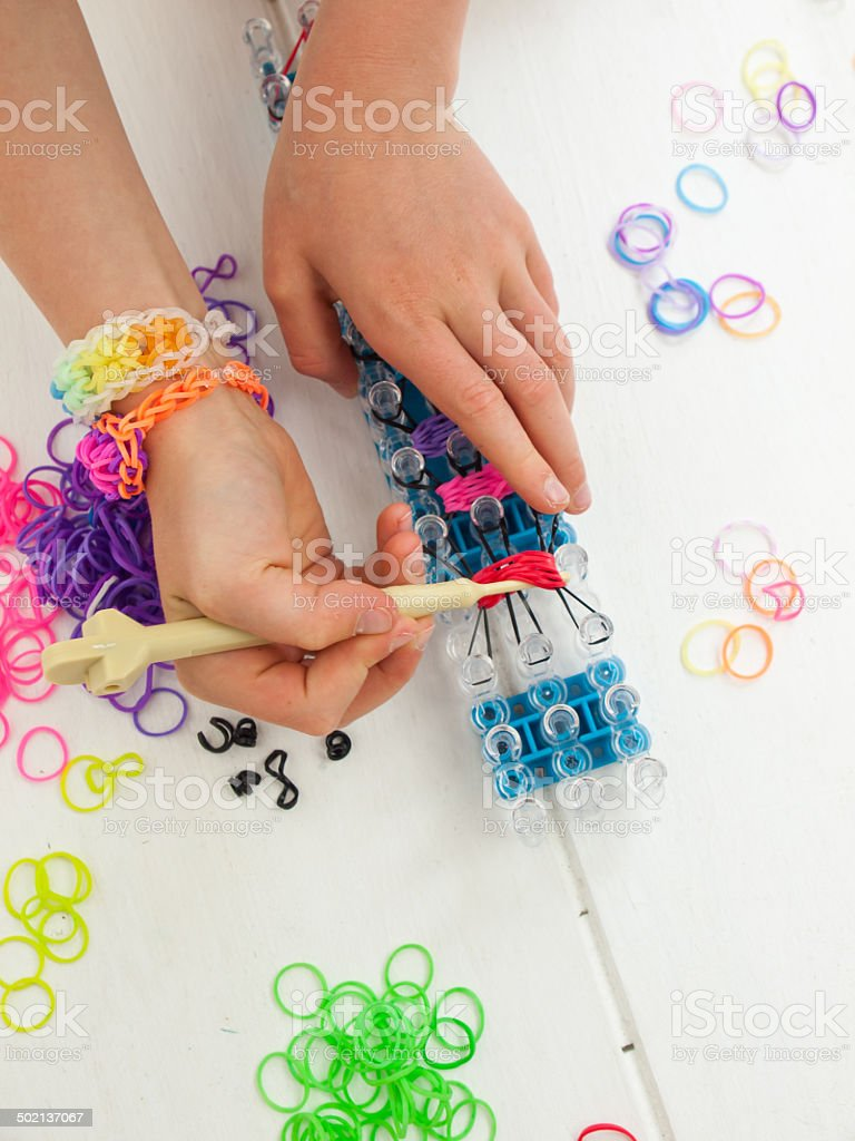 childs hands with band loom stock photo