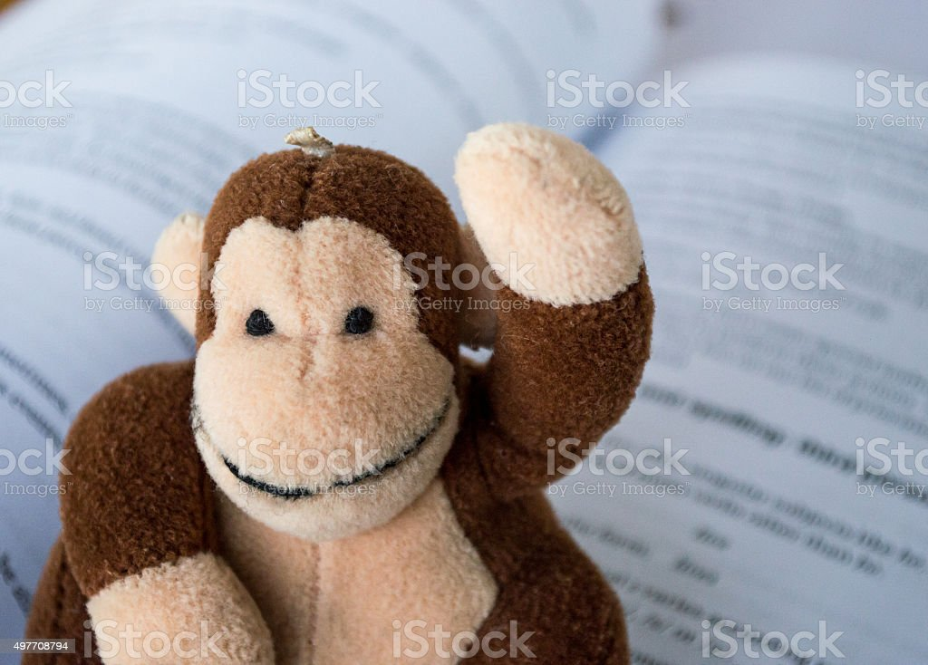 Child's Monkey Toy Raising Hand/Asking a Question Book Background royalty-free stock photo