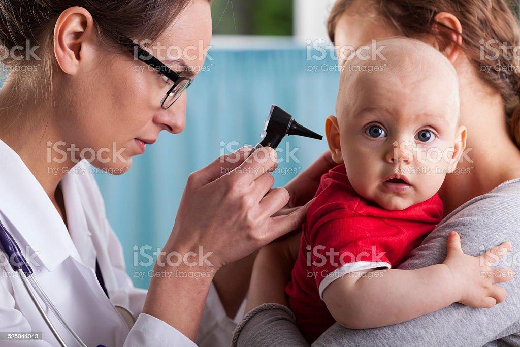 Child's otolaryngologist doing ear examination stock photo