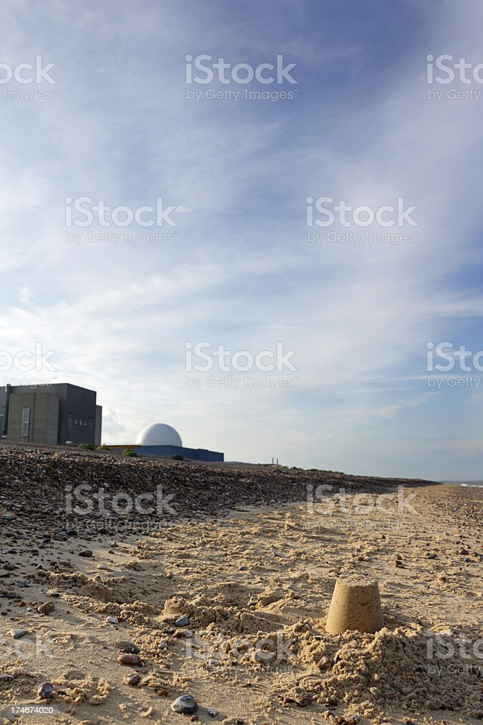 child's sandcastle and nuclear power station stock photo
