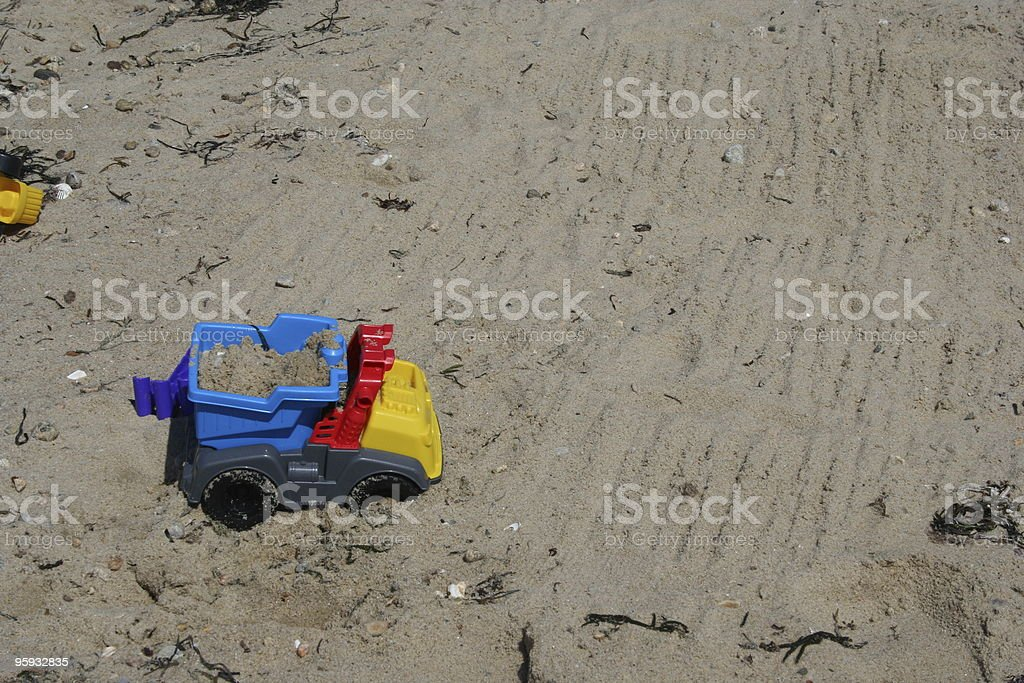 Child's Toy Dump Truck on a Sandy Beach stock photo
