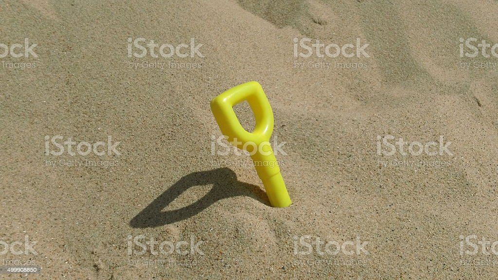 Child's toy spade handle pokes out of sandy beach stock photo