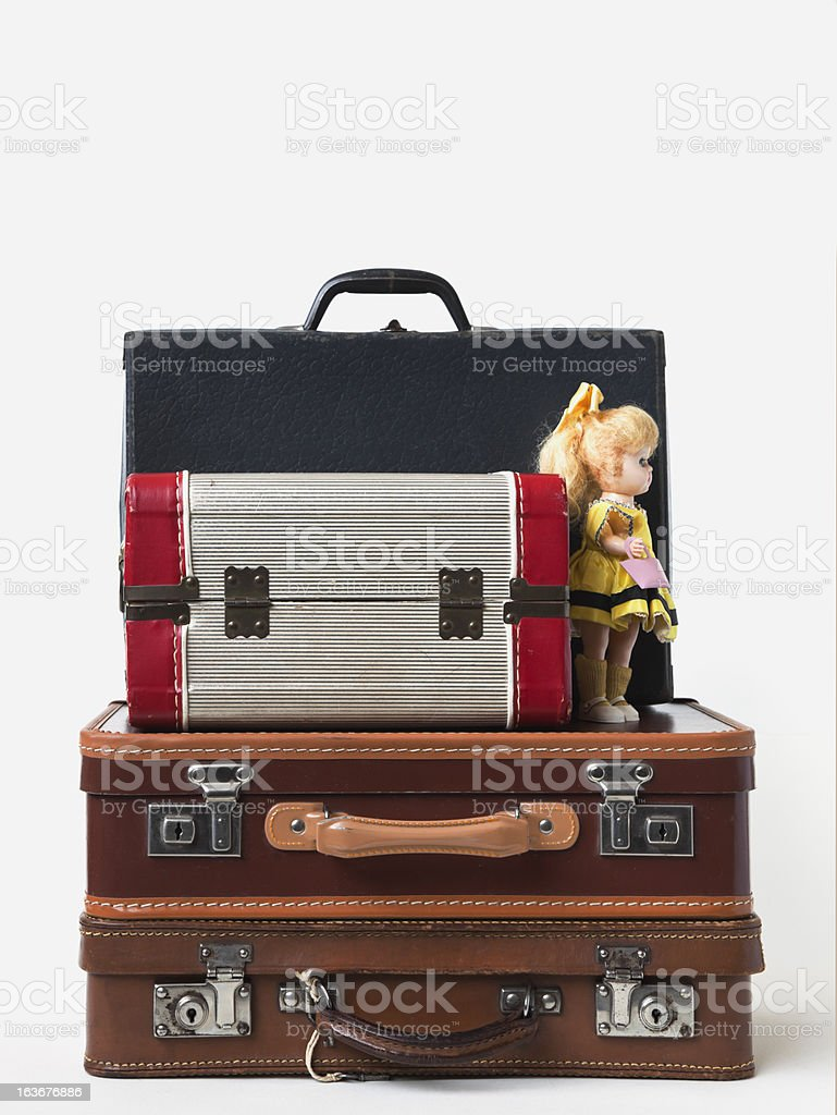 Child's vintage  luggage with doll sitting on top. royalty-free stock photo