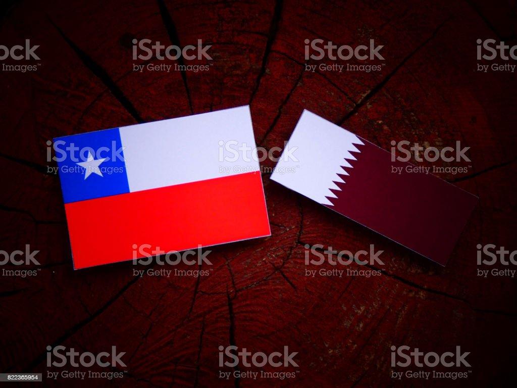 Chilean flag with Qatari flag on a tree stump isolated stock photo