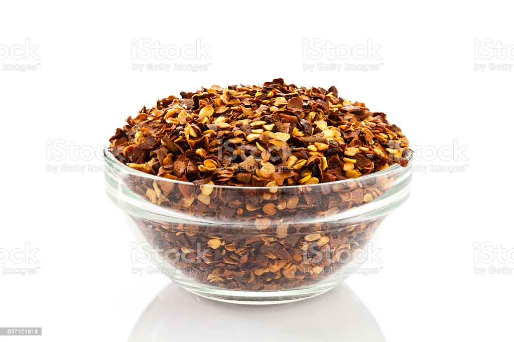 Chili flakes in a glass bowl stock photo