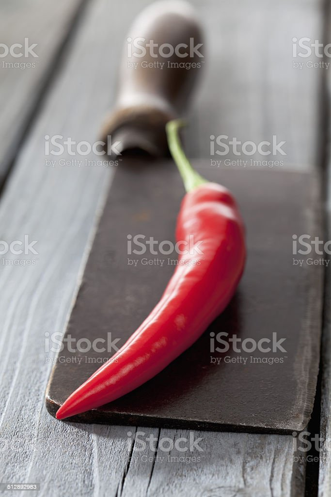 Chili on knife on gray wooden background stock photo