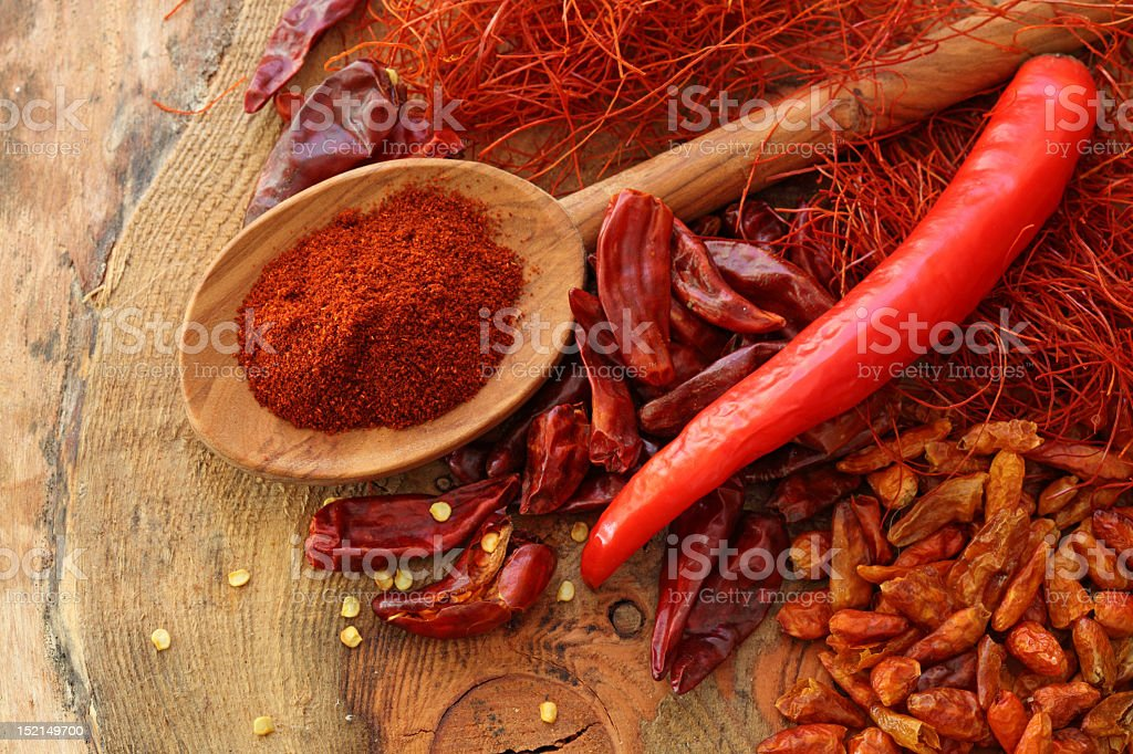 A chili pepper and chili spice on a wooden spoon stock photo