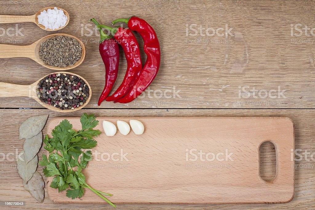 Chili pepper, garlic, bay leaf, spices in spoons on wood royalty-free stock photo