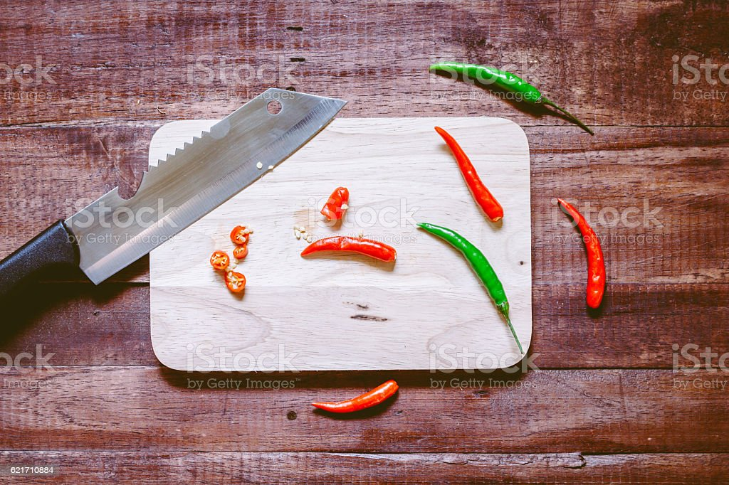 Chili pepper with Knife on chopping board on wooden background stock photo