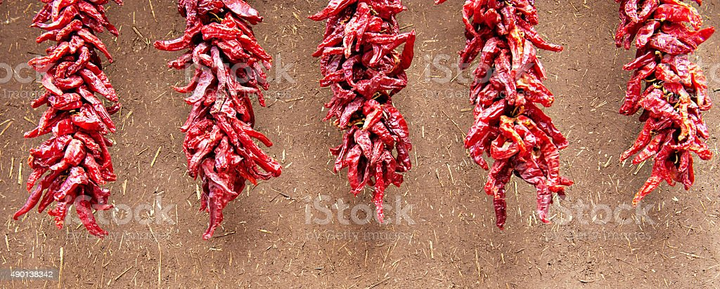 Chili Peppers Ristras on Adobe Wall stock photo
