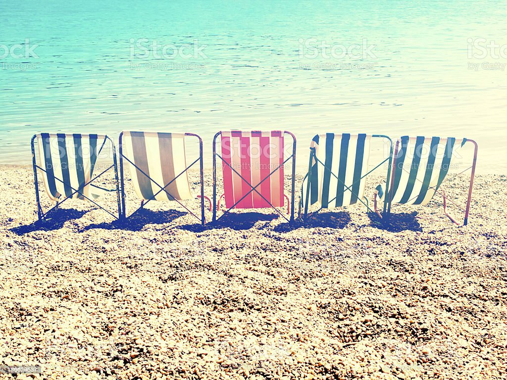 chill on beach with retro stripes sun bed stock photo