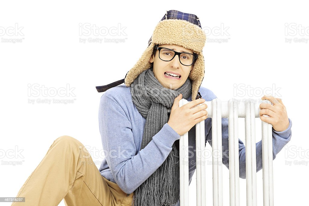 Chilled young man sitting next to a radiator stock photo
