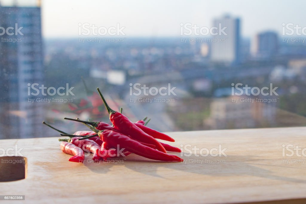 Chilli peppers on cutting board near window in urban setting with blurred background and reflection.  Wooden cutting board with copy space.  Meal ideas and cooking recipe. stock photo