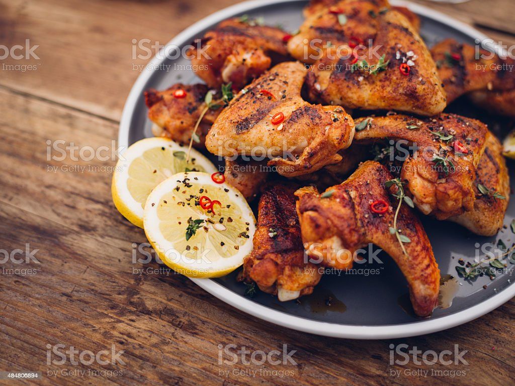 Chillie sprinkled spicy chicken wings on a wooden table stock photo