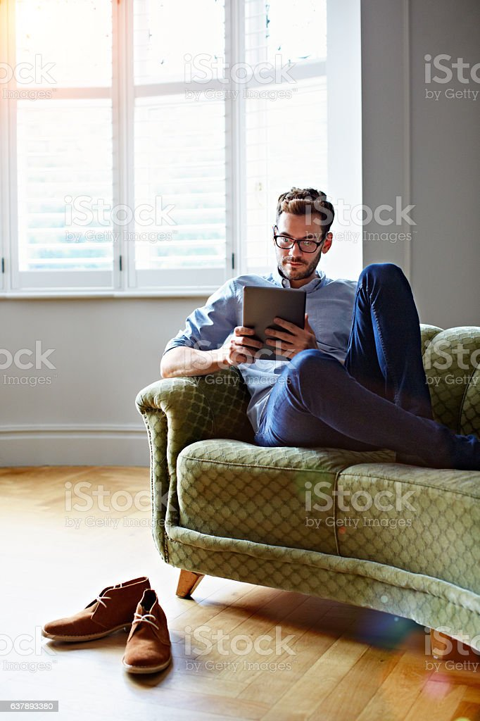 Chilling on the sofa with his tablet stock photo