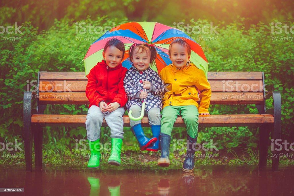 Chilren under umbrella stock photo