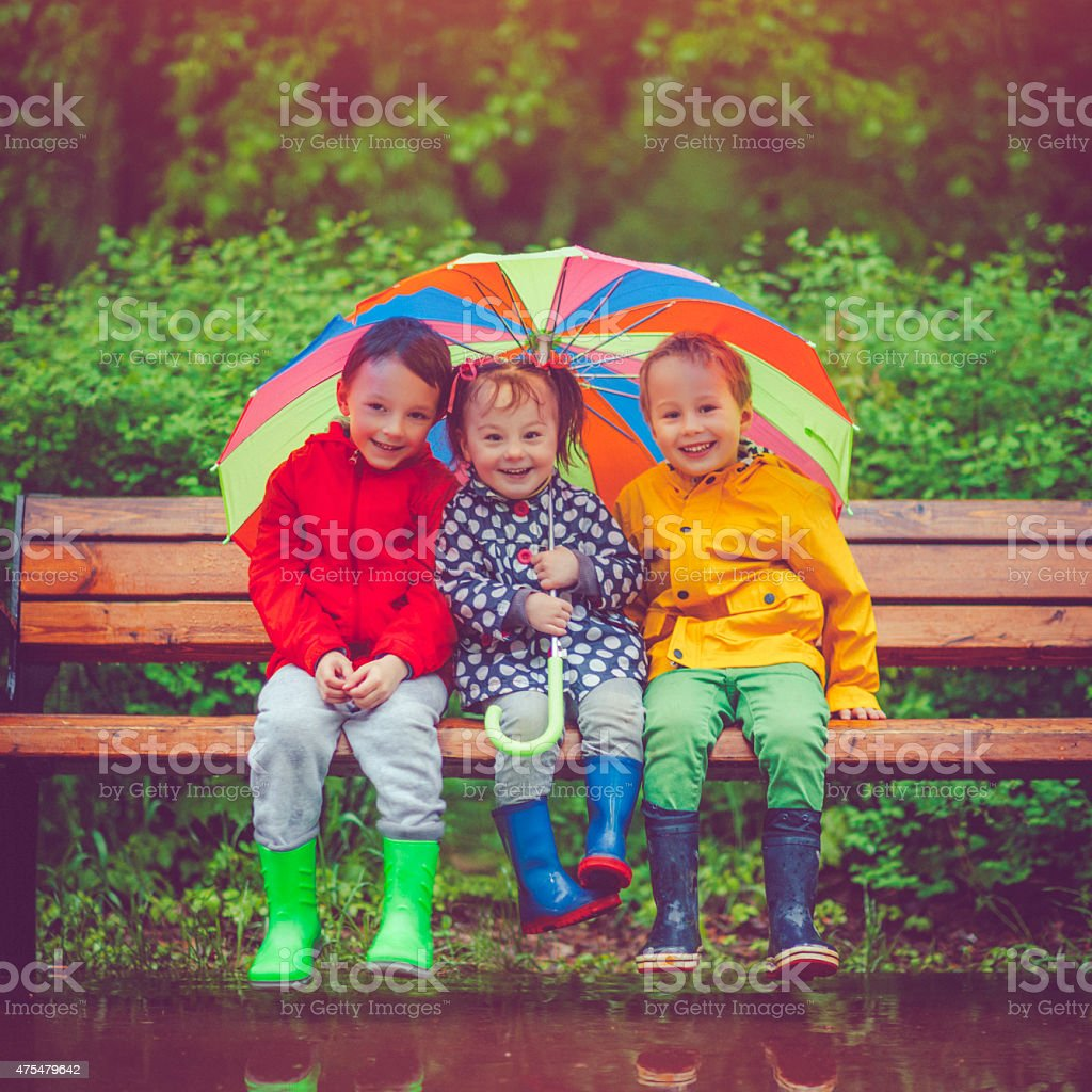Chilren under umbrella stock photo