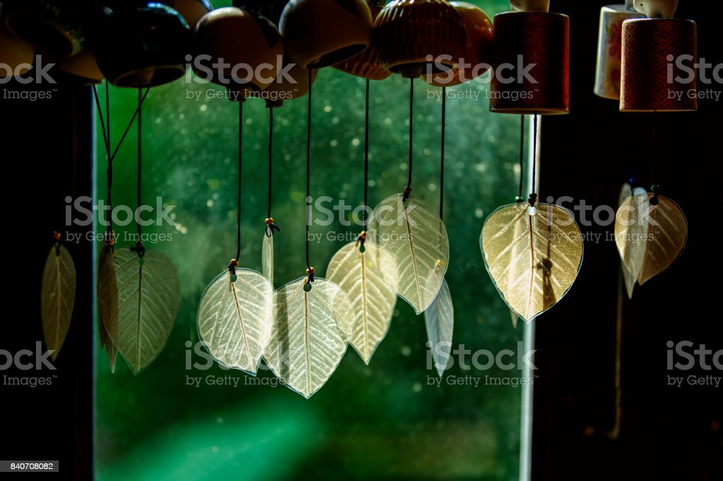Chimes hanging in the window, Decorative bells hang on the window behind with bokeh background, The traditional wind bell fluttering in tropical wind in Thai house. stock photo