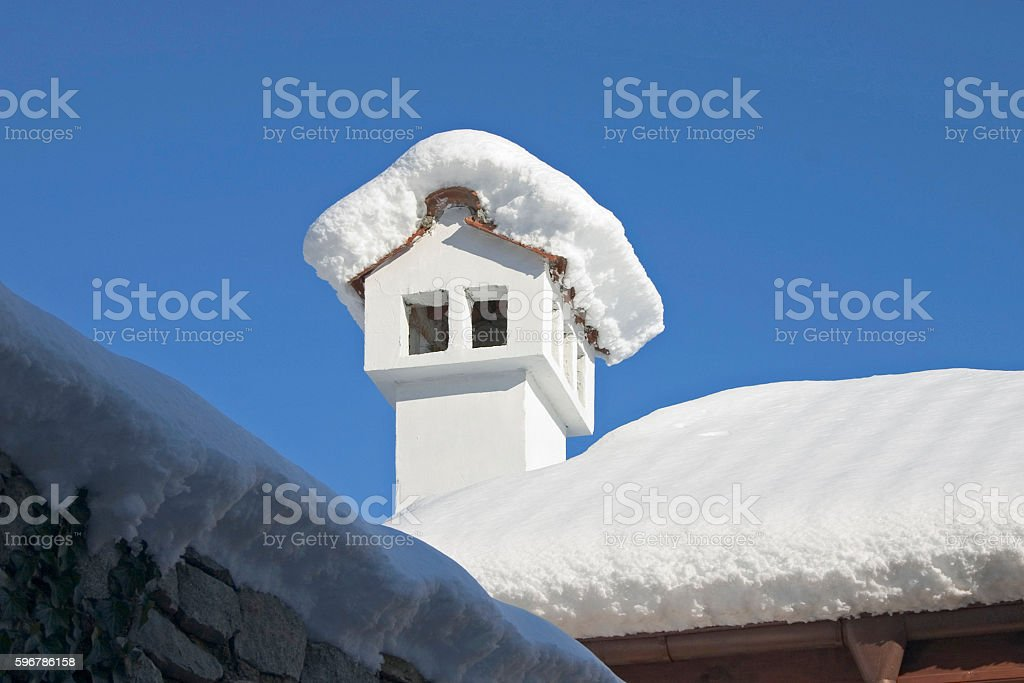 chimney in winter covered with snow stock photo
