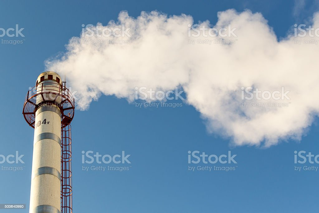 Chimney Pollution Smoke Rising into a Blue Sky stock photo