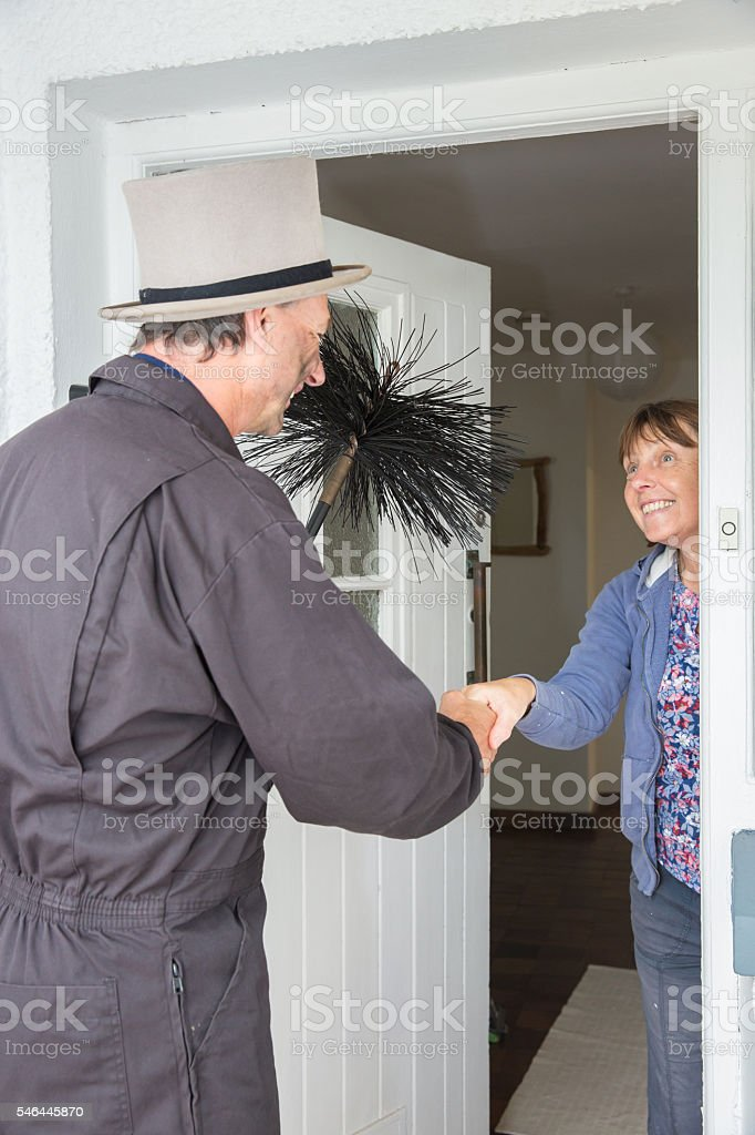 Chimney sweep holding a brush greeting a female customer stock photo