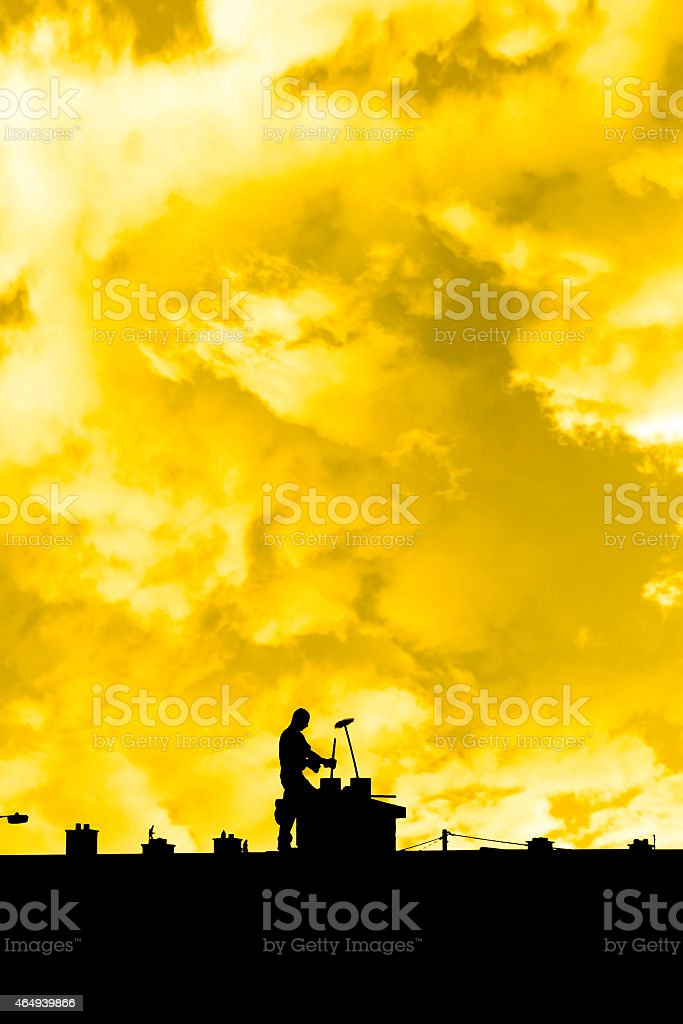 chimney sweep silhouette on the rooftop stock photo